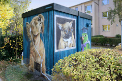 Verteilerkasten einer Energiestation mit Illusionmalerei  / Fassadenbild versehen. Hund mit Kopfhörer oder Brille - Papagei im Ornat in der Sieker Landstraße im Hamburger Stadtteil Rahlstedt.