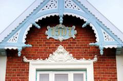Blau und weiß eingefasster Holzgiebel einer Gründerzeitvilla / Wohnhaus mit Stuckdekor und vergoldeter Jahreszahl 1907 als Baudatum am Eichholzfelder Deich im Hamburger Stadtteil Ochsenwerder.