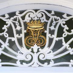 Goldenes Wappen im Oberlicht vom Eingang der Nienstedtener Kirche.