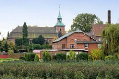 Blick über das Gelände einer Rosenzucht zur St. Pankratius Kirche in Hamburg Ochsenwerder.