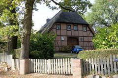 Historisches Wirtschaftsgebäude mit Fachwerk und Reetdach im Hamburger Stadtteil Groß Flottbek  - Holztor als Scheuneneinfahrt; Wohnhaus in der Baron Vogt Straße.