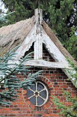 Dachfirst eines Reetdachhauses am Tatenberger Deich in Hamburg Tatenberg rundes Fenster mit Metallrahmen unter dem Dach.