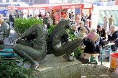 Bronzeskulpturen an der Rahlstedter Bahnhofstraße in Hamburg Rahlstedt - im Hintergrund Marktstände auf dem Wochenmarkt.