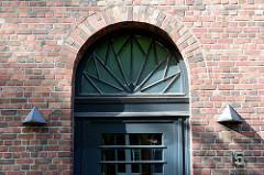 Backsteinarchitektur im Hamburger Stadtteil Uhlenhorst, ehemaliges Verwaltungsgebäude / Fernmeldeamt - errichtet um 1925. Das Gebäude stellt ein Kulturdenkmal Hamburgs dar und ist denkmalgeschützt.  Oberlicht einer  Eingangstür mit expressionistische