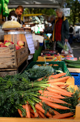 Wochenmarkt in Hamburg Uhlenhorst / Immenhof - Marktstand mit frischem Obst und Gemüse; im Vordergrund Möhren mit Kraut.