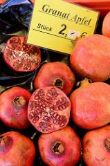 Aufgeschnittene Granatäpfel liegen zum Verkauf in einer Kiste an einem Obststand auf dem Wochenmarkt in Hamburg Blankenese.