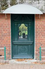 Schwere alte Holztür mit Gründerzeitschnitzereien und schmiedeeisernen Fenstergitter an einem Reetdach Haus im Ochsenwerder Norderdeich im Hamburger Stadtteil Ochsenwerder.