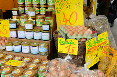 Marktstand mit frischen Eiern und unterschiedlichen Honigsorten auf dem Wochenmarkt in der Möllner Landstraße in Hamburg Billstedt.