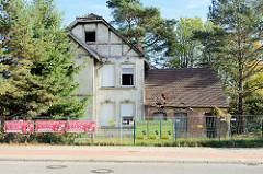 Leerstehende Villa mit Fachwerkgiebel an der Meiendorfer Straße von Hamburg Rahlstedt; das Gelände ist mit Bauzäunen, an denen Werbung hängt, abgesperrt.