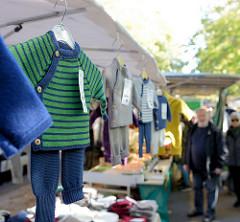 Marktstand mit gestrickter Kinderkleidung auf dem Wochenmarkt Hartzloh im Hamburger Stadtteil Barmbek Nord.