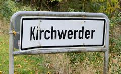 Stadtteilgrenze vom Hamburger Stadtteil Kirchwerder, weißes Schild mit schwarzer Schrift.