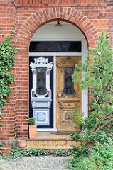 Eingang eines Wohnhauses in Hamburg Ochsenwerder  - mit Schnitzwerk aufwendig dekorierte Holztür, Jugendstildekor; auf der einen Seite frisch restauriert mit farblich abgesetzten Schnitzereien, bei der anderen Türhälfte ist die Farbe abgebeizt.