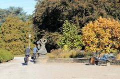 Herbst im Hamburger Stadtpark Winterhude - die Bäume sind herbstlich gefärbt Radfahrer an der Statue tanzende Mädchen von Karl August Ohrt.