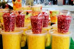Wochenmarkt auf dem Burchardplatz im Kontorhausviertel in dem Hamburger Stadtteil Altstadt. Marktstand mit frischem Obst - Becher mit Granatapfelkernen und geschnittenem Ananas.