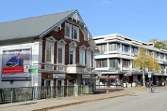Wohnhaus mit Geschäften im Baustil der Gründerzeit am Ufer der Pinnau in der Elmshorner Straße von Pinneberg; dahinter die moderne Architektur der Neuzeit.