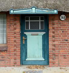 Historische Eingangstür / Holztür mit Schutzdach eines Reetdach Hauses in der Heinrich-Osterath-Straße im Hamburger Stadtteil Kirchwerder.