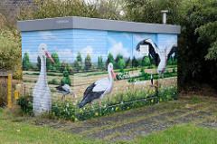 Verteilerkasten einer Energiestation mit Illusionmalerei / Fassadenbild versehen. Weißstörche auf den Kirchwerder Wiesen.