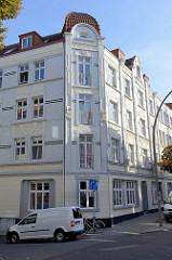 Eckhaus an der Straße Vogelhüttendeich im Hamburger Stadtteil Wilhelmsburg; Jugendstilarchitektur, mehrstöckiges Wohnhaus mit weißglasierten Ziegeln und Jugendstilornamentik.