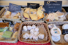 Käsestand auf dem Wochenmarkt Sand im Hamburger Stadtteil Harburg; unterschiedliche Käsesorten z.B.  Ziegen und Schafskäse,  Harzer Roller oder Käse mit Feigen und Aprikosen liegen in kleinen Körben.
