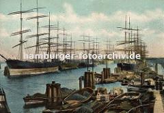 Die Segelschiffe liegen in der Mitte des Hafenbeckens und beim Kai im Hamburger Segelschiffhafen (ca. 1900); im Vordergrund Schuten, die mit Kohle, Kisten oder anderer Ware beladen sind.