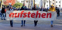 """Aktionstag der überparteilichen Sammlungsbewegung Aufstehen - Start der Demonstration mit dem Motto Würde statt Waffen auf dem Platz der Republik in Hamburg Altona. Transparten mit der roten Aufschrift """"aufstehen""""."""