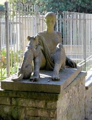 Kunst im öffentlichen Raum, Skulptur Frau mit Hund auf einem Sockel am Eingang zu Schröders Elbpark in Hamburg Othmarschen.