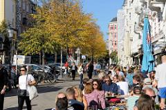 Sonniger Herbstsonntag auf der Piazza im Hamburger Stadtteil Sternschanze; im Szeneviertel Hamburgs haben am Schulterblatt Restaurants und Cafés ihren Gäste Tische in die Sonne gestellt.