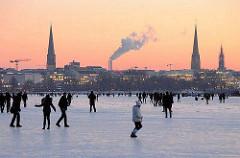Abend an der zugefrorenen Alster - Kirchtürme der Hansestadt Hamburg im Abendrot.