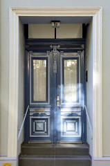 Eingangstür eines denkmalgeschützten Etagenhauses im Compeweg von Hamburg-Harburg. Blau abgesetzte Leisten und Schnitzereien dekorieren die Holztür.