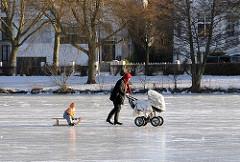 Schlittschuhlaufen auf der zugefrorenen Alster in Hamburg / Mutter mit Kinderwagen  zieht ein Kind mit dem Schlitten.