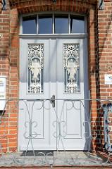 Eingangstür des ehemaligen Verwaltungsgebäude der Elbewerft in der Hamburger Straße von Boizenburg/Elbe. Verziertes Eisengitter mit Engelsfigur und Vögeln vor der Verglasung.