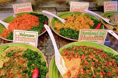 Marktstand mit mediterranen Delikatessen auf dem Wochenmarkt am Moorhof im Hamburger Stadtteil Poppenbüttel;leckerer Hummus und Couscous werden in Schalen angeboten.