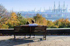 Blick vom Schröders Elbpark im Hamburger Stadtteil Othmarschen auf die Elbe und die Hafenanlage - ein Liebespaar sitzt auf einer Parkbank und genießt den Ausblick, der Mann hat seine Arme weit ausgestreckt.