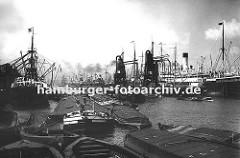 Historische Bilddokumente aus dem Hamburger Hafen.  Blick in den  Hamburger Segelschiffhafen ca. 1930, links wird ein Frachtschiff am Americakai mit Kränen entladen - Motorschiffe und Lastkäne liegen mit ihrer abgedeckten Ladung im Hafenbecken.