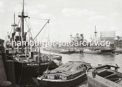 Historische Hafenmotive aus dem Hamburger Fotoarchiv. Frachtschiffe liegen im Segelschiffhafen - der Güterumschlag findet zur Kaiseite mit Kränen statt; zur Wasserseite werden die Waren mit bordeigenen Ladebäumen auf Schuten und Elbkähne geladen