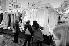 Marktstand mit Stoffen auf dem  Wochenmarkt in der Großen Bergstraße, Stadtteil Hamburg Altona / Altstadt; Schwarzweißfotografie.
