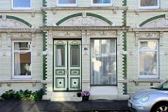 Jugendstil Wohnhaus mit weiß glasierten Kacheln und grünen Bändern im Auedeich von Hamburg Finkenwerder; in dem unter Denkmalschutz stehenden Gebäude war früher eine Bäckerei Konditorei untergebracht.