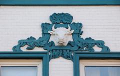 Wohnhaus im Auedeich von Hamburg Finkenwerder; der  Stierkopf mit floralen Reliefdekor am Hausgiebel weist darauf hin, dass früher dort eine Schlachterei ihren Sitz hatte.