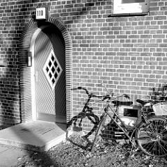 Halbrunde Eingangstür mit rautenförmigen Fenster im Finkenwerder Norderdeich im Hamburger Stadtteil Finkenwerder; ein an der Hauswand angelegtes Damenfahrrad wirft lange Schatten.