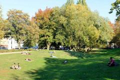 Liegewiese  in der Grünanlage Göhlbachtal im Hamburger Stadtteil Harburg. Parkbesucherinnen liegen auf Decken in der herbstlichen Abendsonne.