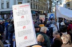 """Aktionstag der überparteilichen Sammlungsbewegung Aufstehen - Abschlusskundgebung der Demonstration mit dem Motto""""Würde statt Waffen"""" auf dem Spitzenplatz von Hamburg Altona; Protestschild."""