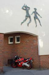 Bronzefiguren, tanzende Frauen als Relief an einer Hausfassade in der Harmsstraße von Hamburg-Harburg; Ein rotes Motorrad ist im Hausdurchgang geparkt.