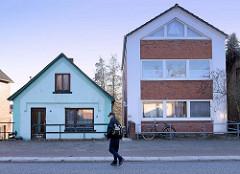 Einzelhaus mit türkisfarbener Fassade neben einem Wohnblock mit Satteldach am Neßdeich von Hamburg Finkenwerder.