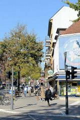 Sonniger Herbstnachmittag eines Sonntages an der Osterstraße  im Hamburger Stadtteil Eimsbüttel. Rechts die Geschäftsräume einer Videothek Ecke Hellkamp.