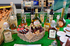 Obststand aus dem Alten Land auf dem Wochenmarkt am Quarree im Hamburger Stadtteil Wandsbek; Flaschen mit Altländer Obstler, Apfelbrand oder Fruchtlikör stehen zum Verkauf bereit.