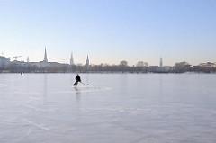 Hamburger Winter - frostiges Winterwetter, Sonnenschein an der zugefrorenen Außenalster.