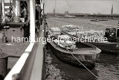 Historische Hafenmotive aus dem Hamburger Fotoarchiv.   Schuten haben am Amerikakai des Segelschiffhafens längsseits eines Frachters festgemacht - eine Ladung Kanthölzer wird auf die Lastkähne gelöscht. Auf der gegenüber liegenden Seite der