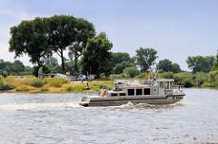 Blick über die Elbe zum Fähranleger Bleckede der Autofähre Amt Neuhaus;  das Motorboot X-Ray fährt im abwärts