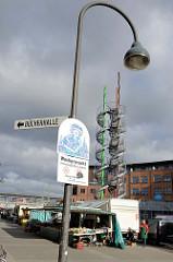 Wochenmarkt auf dem Fleetplatz in Hamburg Allermöhe, Hinweisschild auf die Marktzeiten. Im Hintergrund die Wendeltreppen der sogenannten Zuckerstangen ein Kunstprojekt des Stadtteils. Das begehbare Kunstwerk hat eine Höhe von 25 m, Künstler Michael D