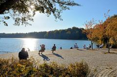 Herbsttag  an der Promenade der   Außenmühle im Stadtpark von Hamburg Harburg;  sonnenhungrige Parkbesucherinnen  sitzen auf Einzelstühlen am See in der Sonne. Die die Blätter von Bäumen und Sträuchern sind herbstlich gefärbt.
